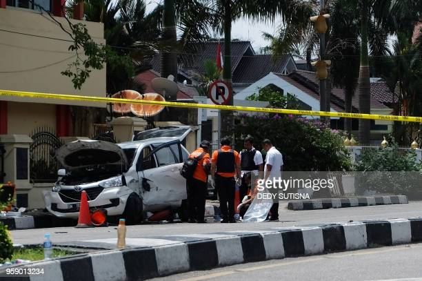 TOPSHOT Indonesian policemen examine a car used by attackers outside the police headquarter in Pekanbaru Riau following attacks on May 16 2018 Four...