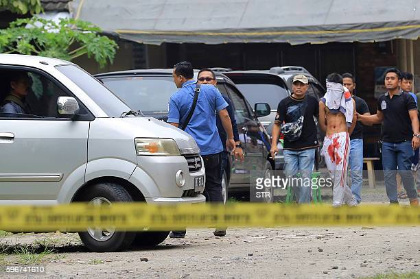 Indonesian policemen guard a blindfolded suspect who attacked a priest in Medan on August 28 2016 A knifewielding attacker in Indonesia stabbed a...