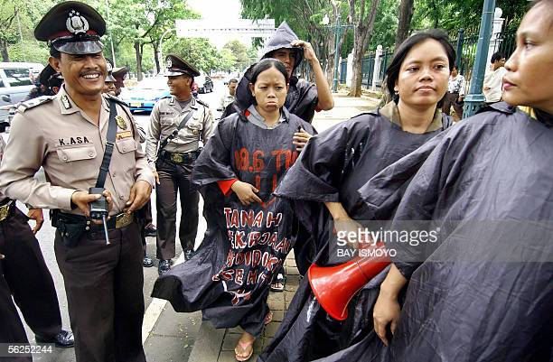 Indonesian policemen laugh at demonstrators protesting against the high price of fuel in Jakarta 22 November 2005 As part of the Jakarta government's...