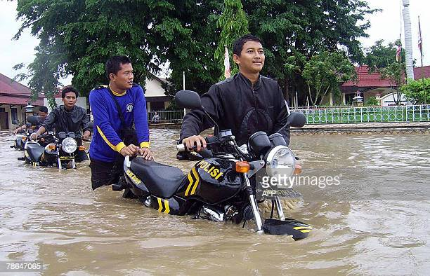 Indonesian policemen push their motorbikes through a flooded street in the Madiun district of East Java province 26 December 2007 At least 10 people...