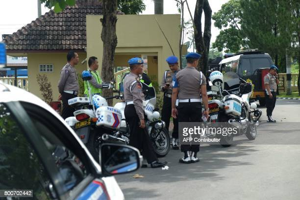 CORRECTION Indonesian policemen stand guard at a security post in North Sumatra's police headquarters in Medan city on June 25 after two attackers...