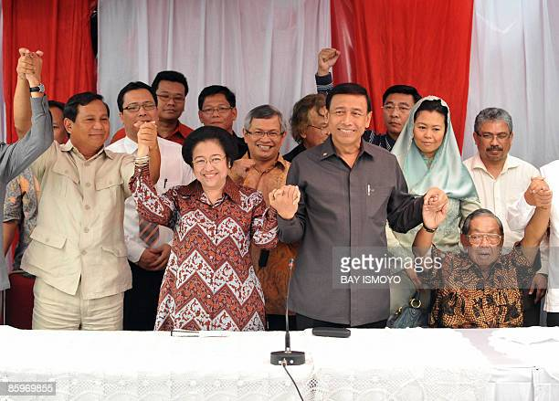 Indonesian political leaders Prabowo former president Megawati Sukarnoputri Wiranto and former president Abdurrahman Wahid join hands during a press...