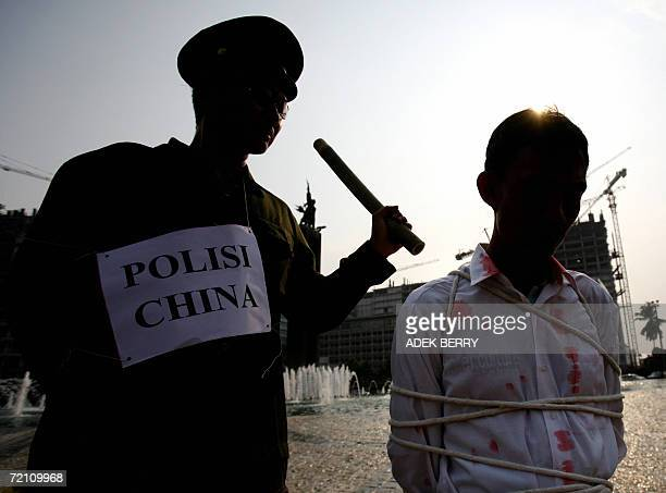 Indonesian practitioners of Falung Gong or Falun Dafa act out a scene of Chinese police torturing people during a protest in Jakarta, 07 October...