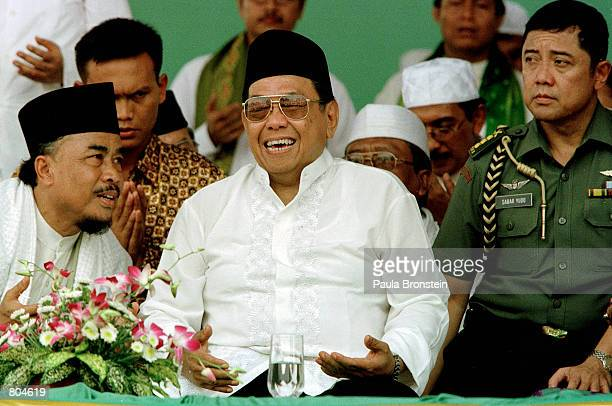 Indonesian President Abdurrahman Wahid laughs with officials as he participates in a mass prayer rally April 29 2001 in Jakarta The embattled Muslim...