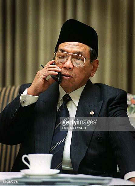 Indonesian President Abdurrahman Wahid talks on the mobile phone prior to a meeting with British Foriegn Secretary Robin Cook in London 01 February...