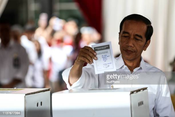 Indonesian President Joko quotJokowiquot Widodo give their votes during the election at a polling station in Jakarta Indonesia on April 17 2019 Tens...