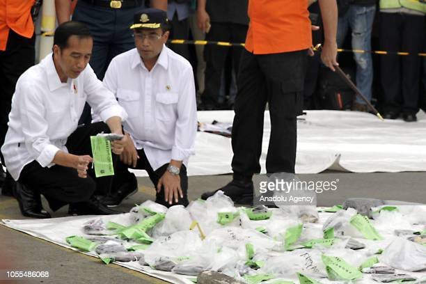 Indonesian President Joko Widodo accompanied by Indonesian Minister of Transportation Budi Karya Sumadi checks the items evacuated from the crashed...