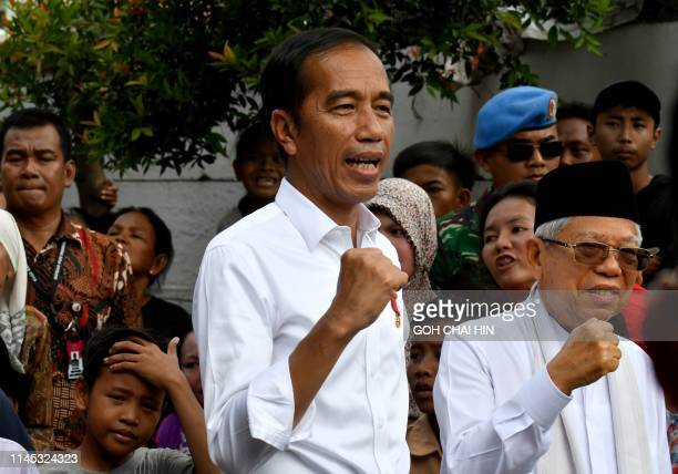 Indonesian President Joko Widodo and his running mate Ma'ruf Amin gesture while visiting a neighbourhood in Jakarta on May 21, 2019. - Thousands of...