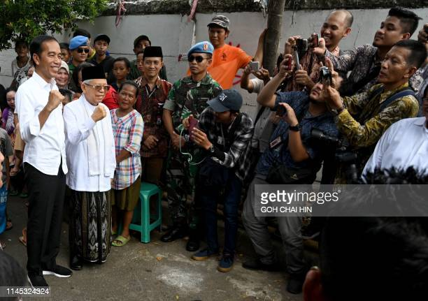 Indonesian President Joko Widodo and his running mate Ma'ruf Amin pose while visiting a neighbourhood in Jakarta on May 21, 2019. - Thousands of...