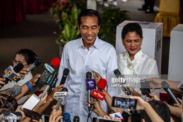 Indonesian President Joko Widodo and his wife Iriana speak to journalists after casting his ballot at a polling station on April 17, 2019 in Jakarta,...