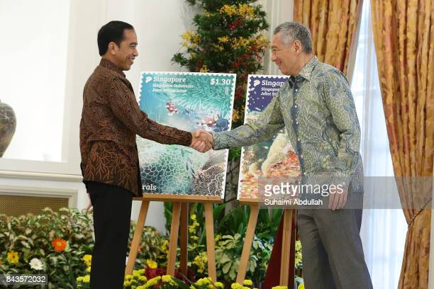 Indonesian President Joko Widodo and Singapore Prime Minister Lee Hsien Loong shake hands after the unveiling the launch of the Joint Stamp Issue at...