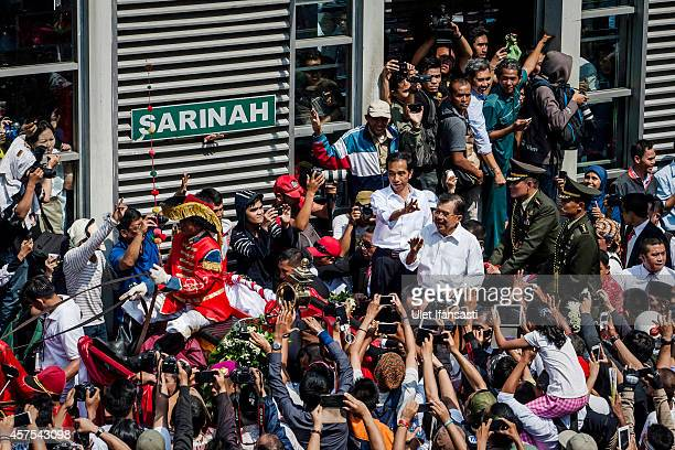 Indonesian President Joko Widodo and Vice President Jusuf Kalla wave to the crowd while on his journey to Presidential Palace by carriage during the...