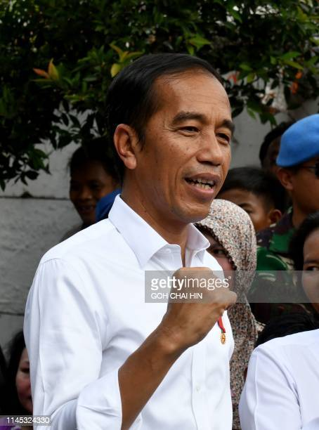 Indonesian President Joko Widodo gestures while visiting a neighbourhood in Jakarta on May 21, 2019. - Thousands of soldiers fanned out across...