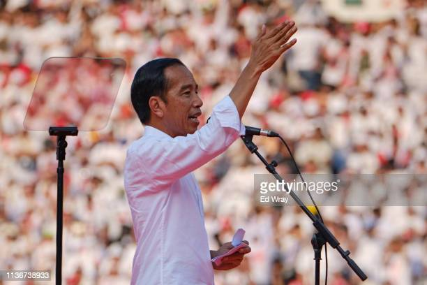 Indonesian President Joko Widodo popularly known as Jokowi gives a speech to supporters at a rally at Jakarta's main stadium on April 13 2019 in...