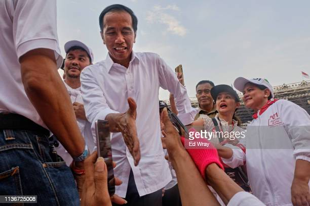 Indonesian President Joko Widodo popularly known as Jokowi shakes hands with supporters at a rally at Jakarta's main stadium on April 13 2019 in...