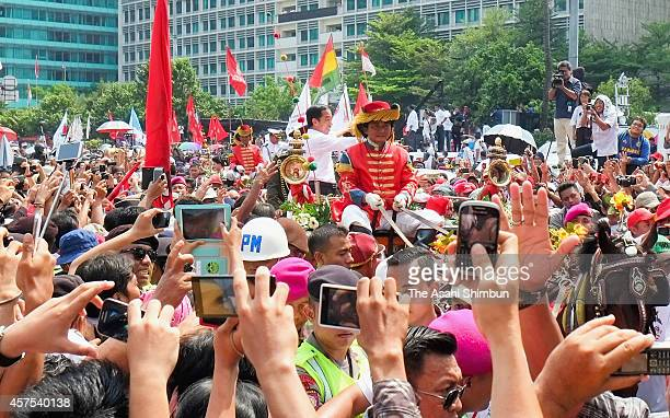 Indonesian President Joko Widodo waves to crowds while on his journey to Presidential Palace during the ceremony parade on October 20 2014 in Jakarta...