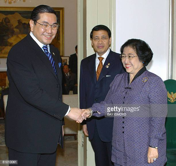 Indonesian President Megawati Sukarnoputri greets Thailand's Foreign Minister Surakiart Sathirathai upon his arrival at the presidential palace for...