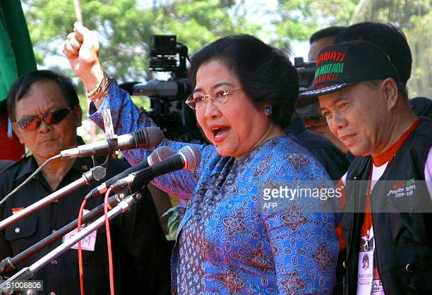 Indonesian President Megawati Sukarnoputri holds her fist into the air during a speech in Manado, North Sulawesi, 29 June 2004, only six days before...