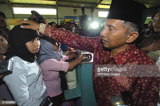 Indonesian presidential candidate Amien Rais consoles a returnee after hearing about her bad experiences from her trip overseas as he visits an...