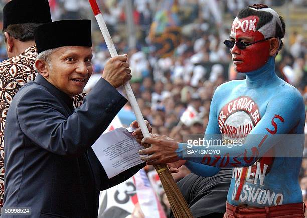 Indonesian presidential candidate Amien Rais holds a broom stick to symbolize his desire to wipe out corruption during his campaign at Bung Karno...