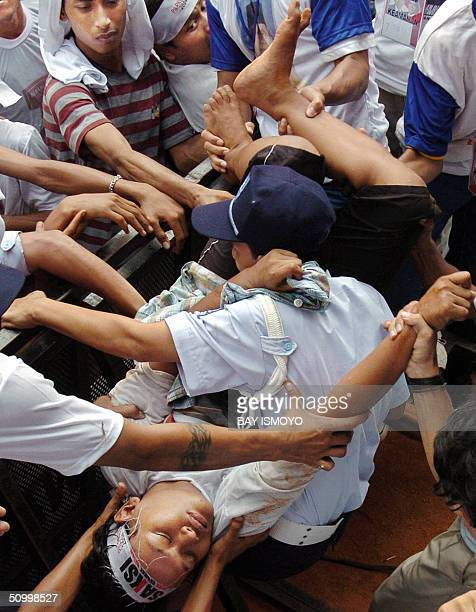 Indonesian presidential candidate Amien Rais supporters try to help a collapsed man from the crowd during the campaign at Bung Karno stadium in...