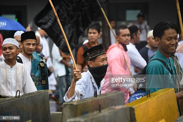 Indonesian protesters march down the capital city's main street after a demonstration at Jakarta's National Monument Park on December 2 2016 More...