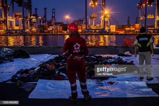 A indonesian red cross member stands in front of recovered personal items from Lion Air flight JT 610 at the Tanjung Priok port on October 30 2018 in...
