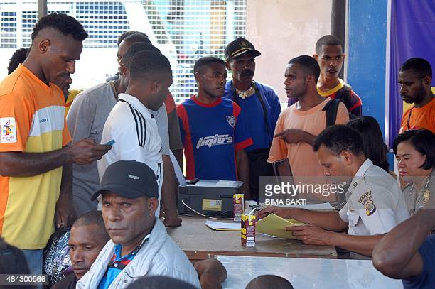 Indonesian relatives submit information to police forensic personnel at a crisis center set up in Jayapura on August 17 2015 following the crash of a...