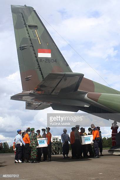 Indonesian rescue personnel load coffins bearing bodies recovered from the underwater wreckage of illfated AirAsia flight QZ8501 on a military plane...