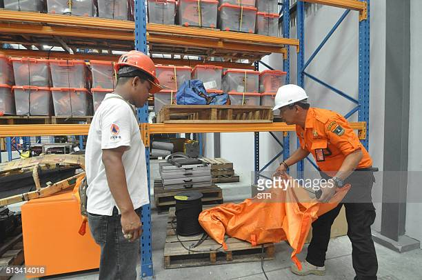 Indonesian rescue team officials prepare at their logistics warehouse in Padang West Sumatra province on March 3 as they wait for updates from remote...