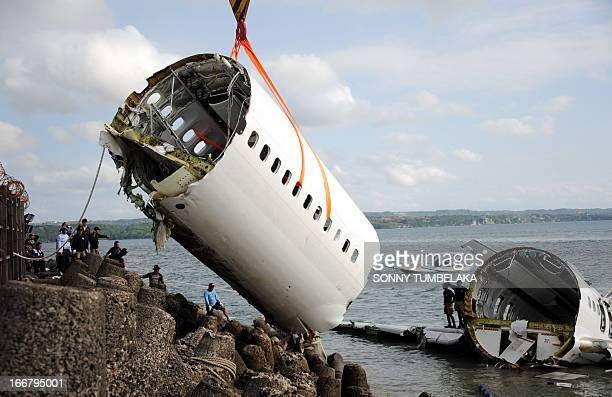 Indonesian rescue workers help remove a section of a Lion Air Boeing 737 from the sea four days after it crashed while trying to land at Bali's...
