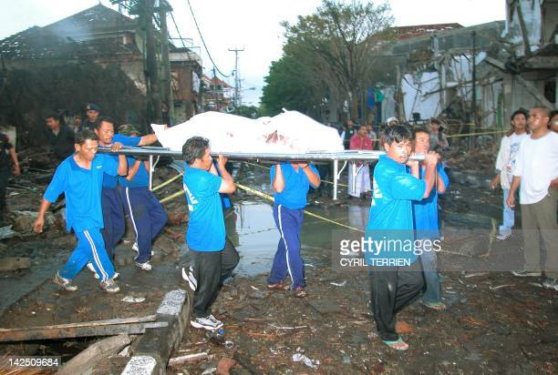 Indonesian rescue workers remove bodies at the site of a bomb blast in the tourist area of Kuta Bali 13 October 2002 At least 150 people have been...