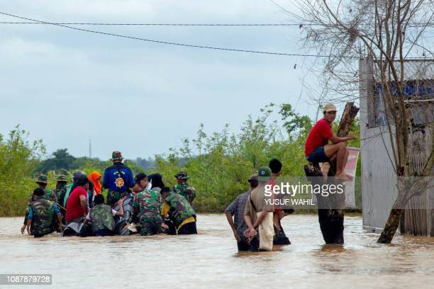 Indonesian rescuers evacuate residents from their homes in Makassar on January 24 2019 as heavy rain and strong winds pounded the southern part of...