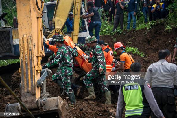 Indonesian rescuers recover the body of a woman from the scene after a wall of mud slammed onto houses from a hillside following heavy rainfall in...