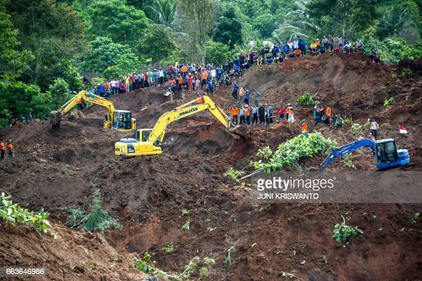 TOPSHOT Indonesian rescuers search for survivors after a wall of mud slammed onto houses from a hillside after heavy rainfall in Ponorogo district...