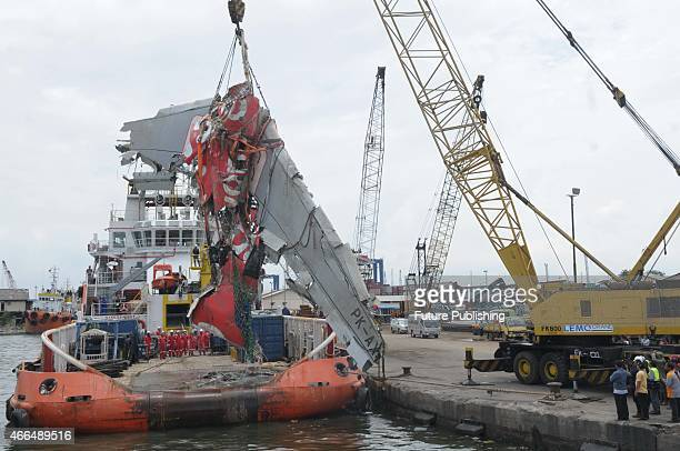 Indonesian rescuers stand next to the remains of the fuselage of crashed Airasia flight QZ8501 on board of the Crest Onyx ship after it was hoisted...