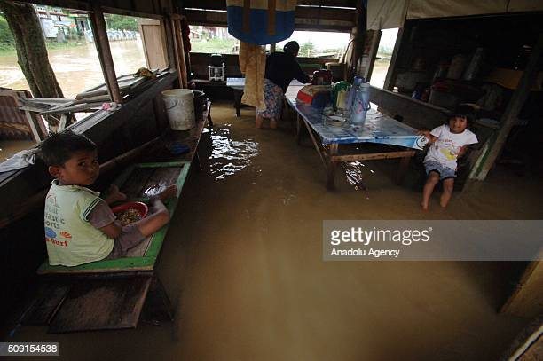 Indonesian residents are seen after torrential rains caused floods at Pangkalan village on February 09 2016 in Lima Puluh Koto regency West Sumatra...