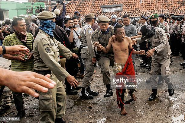Indonesian residents clash with public order agency security officers during the demolition of illegal houses at a slum area on April 11 2016 in...