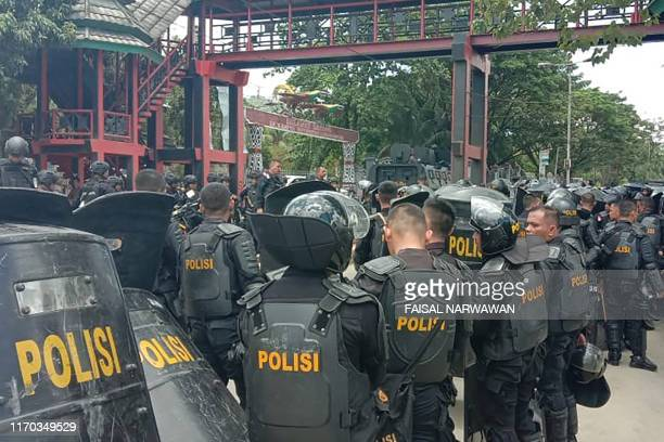 Indonesian riot police take positions at a university in provincial capital Jayapura on September 23 as fresh protests break out in the restive...