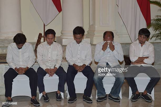 Indonesian sailors attend a ceremony to mark the hostages being handed over to thier families at the Foreign Ministry office in Jakarta on May 2...