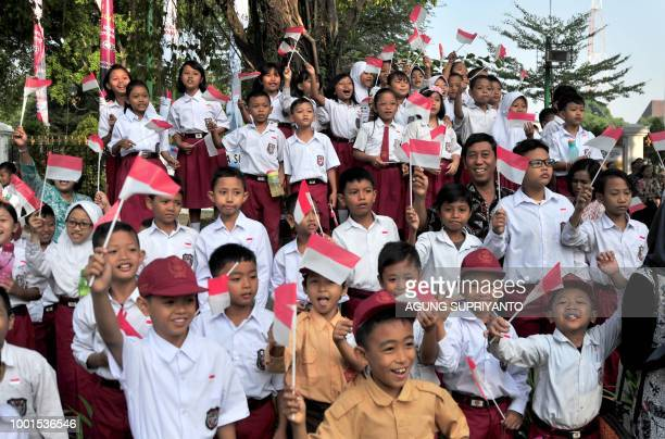 Indonesian school children wave national flags as they watch the torch relay of the Asian Games in Yogyakarta on July 19 2018 Jakarta and Palembang...