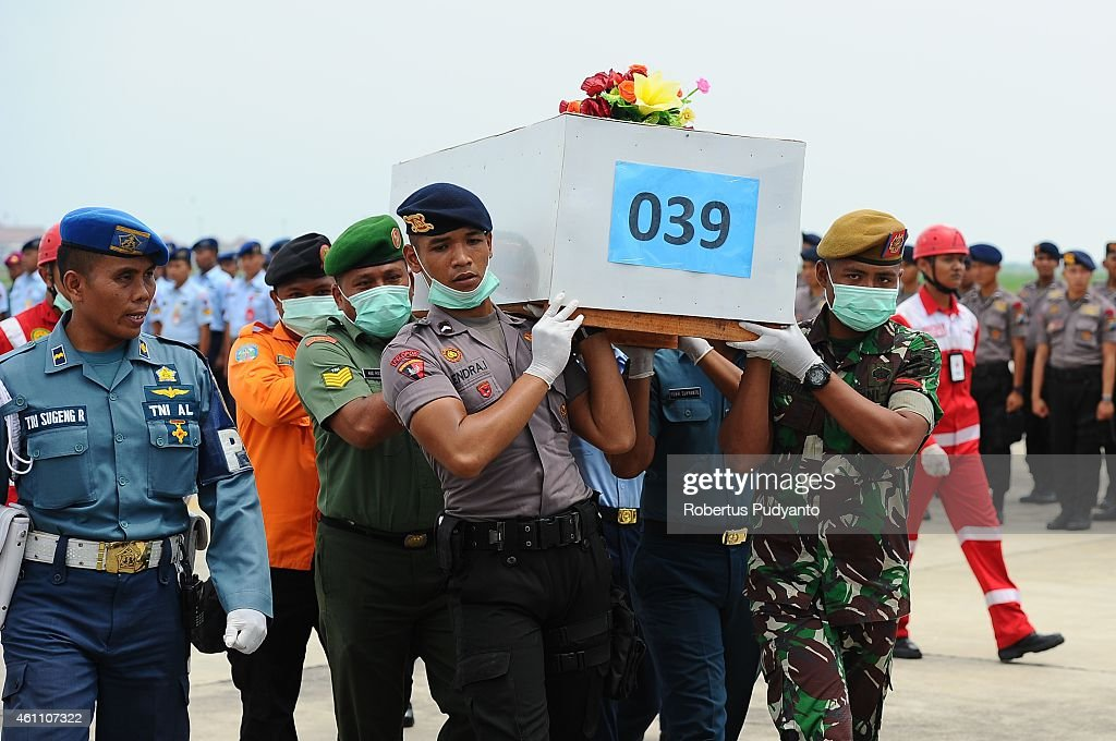 Indonesian Search and Rescue personnel carry the 39th coffin containing a victim of the AirAsia flight QZ8501 disaster on January 7, 2015 in Surabaya, Indonesia. A massive recovery operation is underway in waters off Borneo to recover bodies and debris from the missing AirAsia plane. AirAsia announced that flight QZ8501 from Surabaya to Singapore, with 162 people on board, lost contact with air traffic control at 07:24 a.m. local time on December 28.
