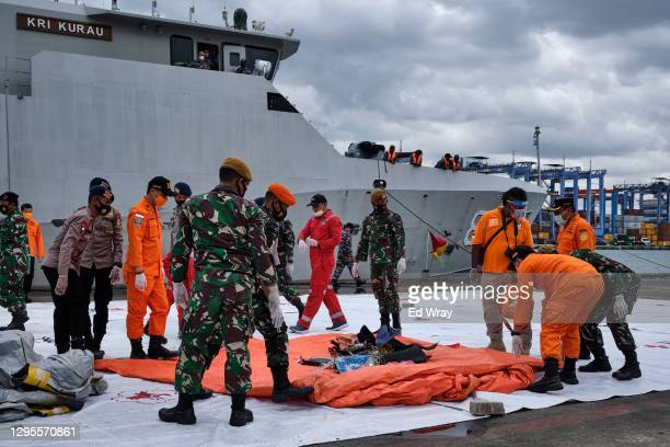 Indonesian search and rescue personnel move a tarpaulin filled with debris from Sriwijaya Air flight SJ182 to be examined by investigators on January...