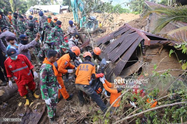 Indonesian search and rescue personnel recover a body in Manuju subdistrict, Gowa regency, South Sulawesi on January 30 following flooding and...