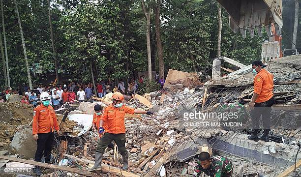 Indonesian search and rescue personnel work as they attempt to rescue people trapped under the rubble of a collapsed building following an earthquake...