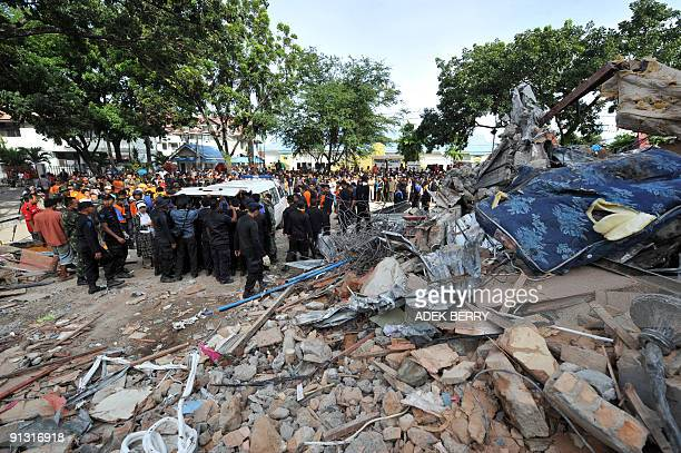 Indonesian search and rescue team members put the dead body of a victim into a vehicle as they continue their rescue operations around collapsed...