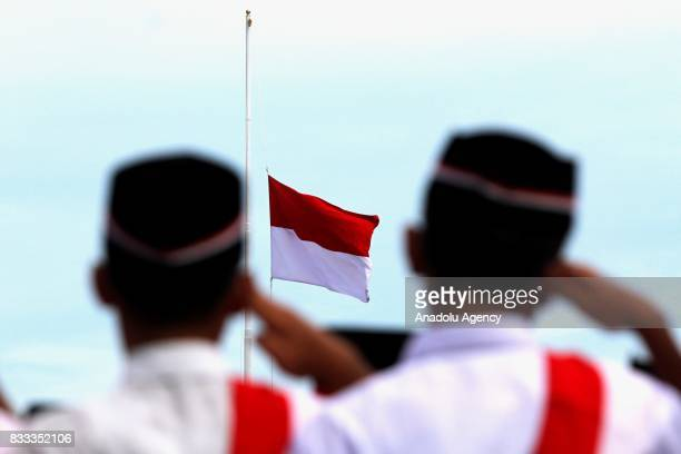 Indonesian security forces salute an Indonesian flag during a ceremony marking Indonesia's 72nd Independence Day at Blang Padang in Aceh Indonesia on...