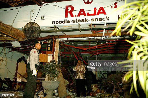 Indonesian security personnel survey the scene at a bomb damaged resteraunt in Kuta on the island of Bali 01 October 2005 At least 23 people were...
