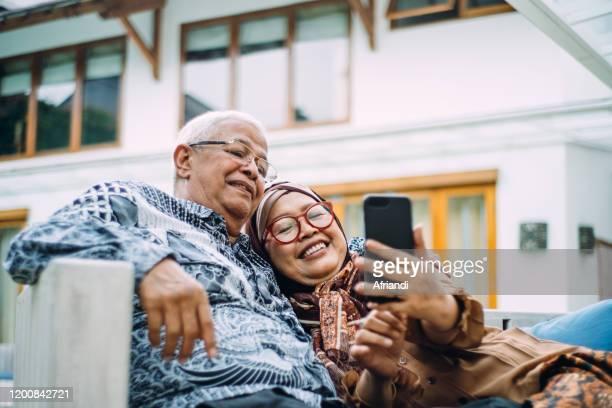 indonesian senior citizens taking a selfie - indonesien stock-fotos und bilder