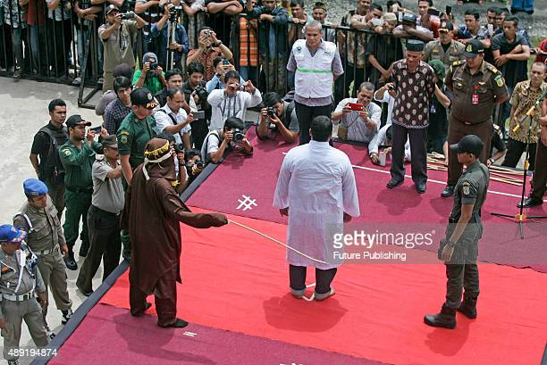 Indonesian Sharia police whips a man during a public caning ceremony outside a mosque on September 18 2015 in Banda Aceh Indonesia Three women and 14...